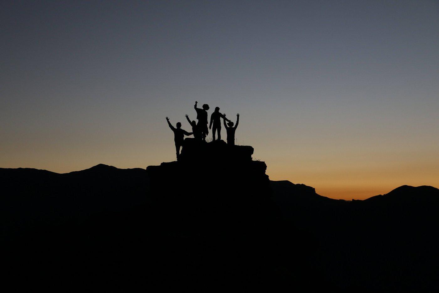 Im Vordergrund eine silhouette einer Gruppe Menschen, auf einem Stein stehen im Hintergrund geht die Sonne unter.
