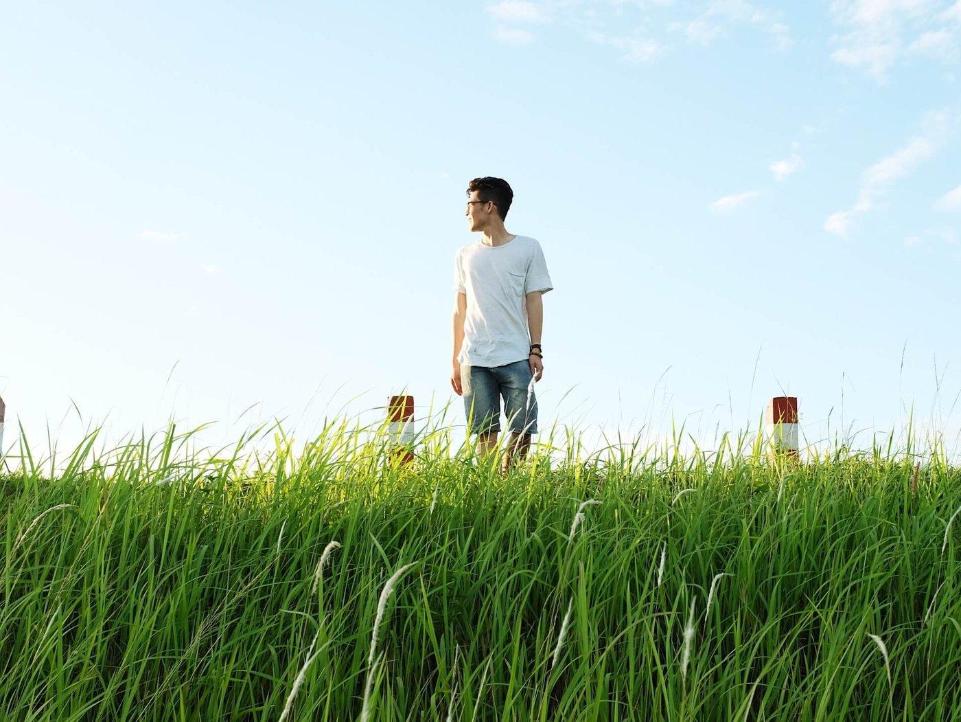Eine grüne Wiese und ein blauer Himmel, auf der Wiese steht ein junger Mann